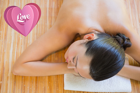 massage  table: Content brunette relaxing on massage table against love heart