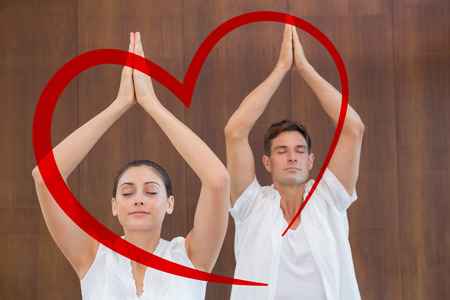 tree position: Peaceful couple in white doing yoga together with hands raised against heart Stock Photo