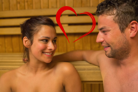 Cheerful couple relaxing in a sauna and chatting against heart photo