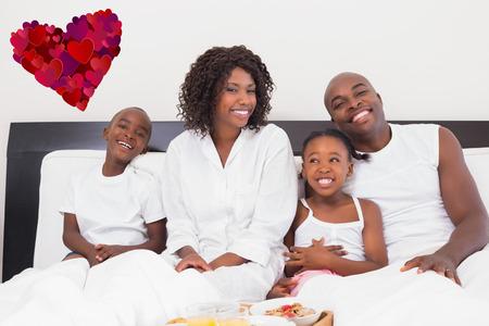 ni�os negros: Familia feliz que desayuna en la cama contra el coraz�n Foto de archivo