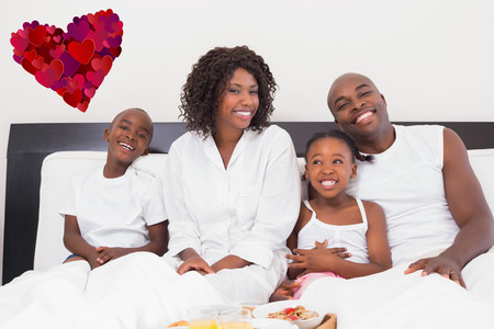 Happy family having breakfast in bed against heart photo