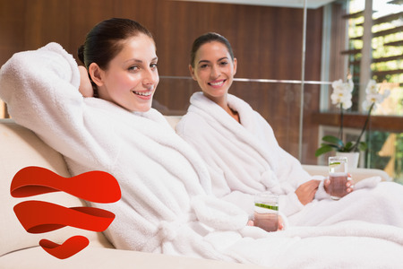 Smiling women in bathrobes sitting on couch against heart photo