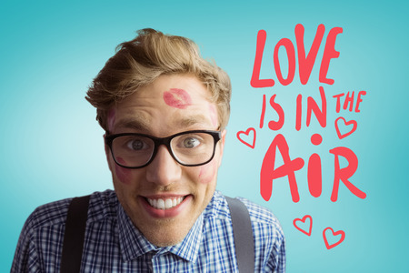 Geeky hipster covered in kisses against blue vignette background photo