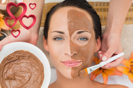 Peaceful brunette getting a mud facial applied against pink hearts photo