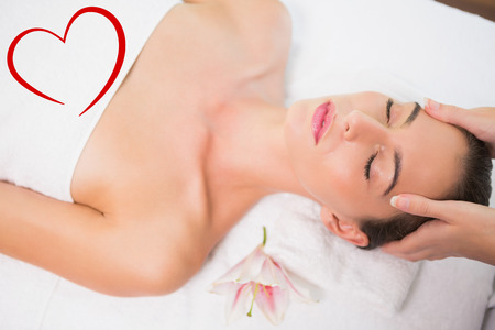 massage table: Attractive woman receiving head massage at spa center against heart