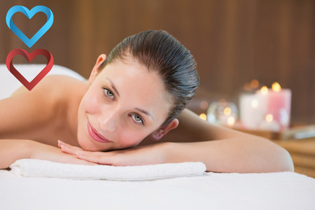 Beautiful woman lying on massage table at spa center against hearts photo