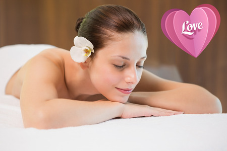 Beautiful woman lying on massage table at spa center against love heart photo