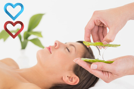 Attractive young woman receiving aloe vera massage at spa center against hearts