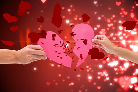 broken up: Hands holding two halves of broken heart against valentines heart design Stock Photo