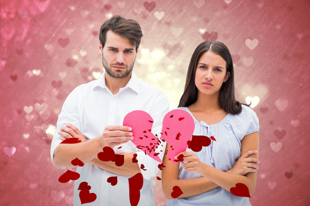 exasperated: Upset couple holding two halves of broken heart against valentines heart design