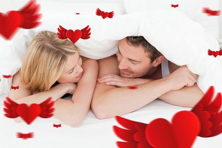 amantes en la cama: Pares encantadores en su cama contra corazones Foto de archivo