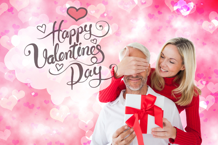 girly: Loving couple with gift against digitally generated girly heart design