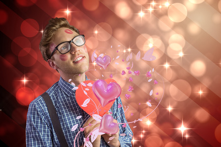 Geeky hipster covered in kisses against light design shimmering on red photo