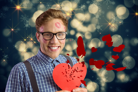 Geeky hipster covered in kisses against shimmering light design on black photo