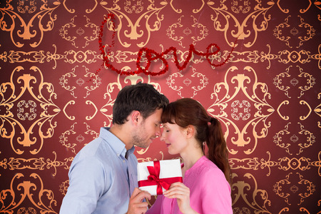 Loving couple holding a gift against elegant patterned wallpaper in red and gold photo