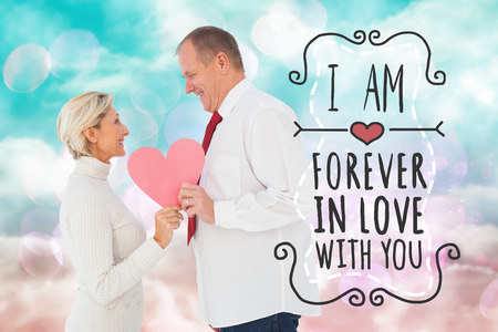 girly: Older affectionate couple holding pink heart shape against digitally generated pink and blue girly design Stock Photo