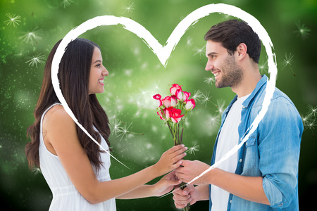 Happy hipster giving his girlfriend roses against digitally generated dandelion seeds on green background photo