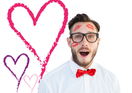 Geeky hipster with kisses on his face against valentines love hearts photo