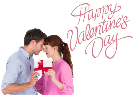 Loving couple holding a gift against cute valentines message photo