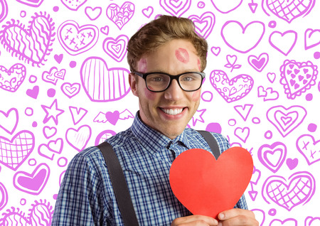 Geeky hipster covered in kisses against heart pattern photo