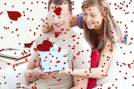 Smiling woman giving a present to her boyfriend against love heart pattern photo
