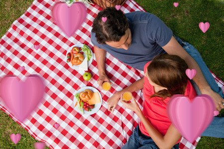 Elevated view of two friends lying on a blanket with a picnic against hearts photo