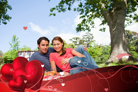 Two friends looking ahead while they hold glasses as they have a picnic against valentines heart design photo