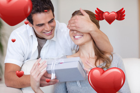 Man covering the eyes of his girlfriend while giving her a present against love heart pattern photo