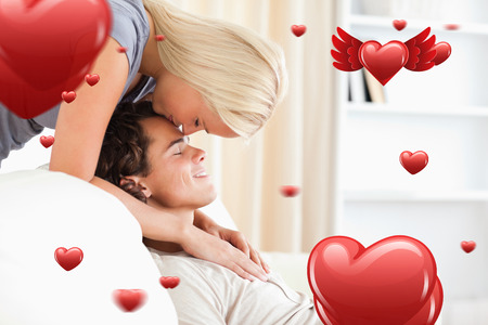 fiance: Woman kissing her fiance on the forehead against love heart pattern Stock Photo