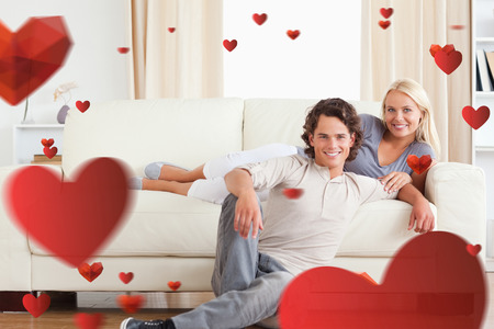 Cute couple posing against love heart pattern photo