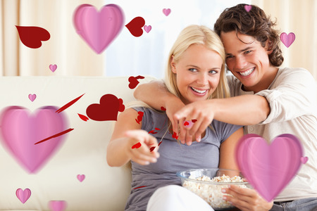 Cute couple watching TV while eating popcorn against love heart pattern photo