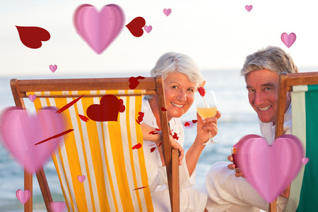 Senior couple drinking a cocktail against love heart pattern photo