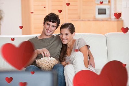 romantic couple: Couple with popcorn on the sofa watching a movie against hearts