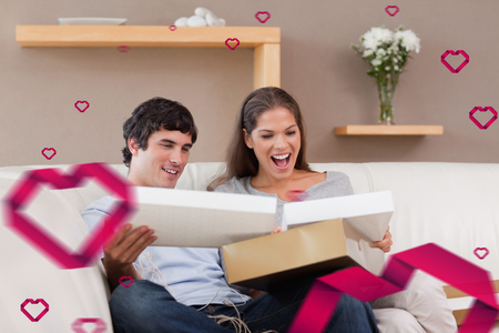 couple on couch: Couple on the couch opening parcel against hearts