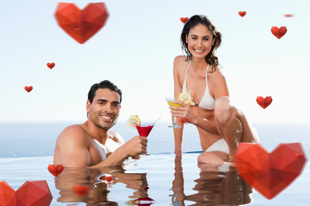 Cheerful couple having cocktails in the pool against hearts photo