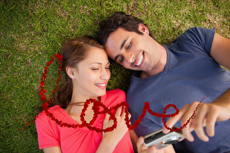 Two smiling friends looking at photos on a camera  against love spelled out in petals photo