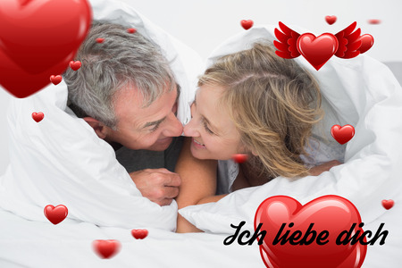 in liebe: Loving middle aged couple under the duvet against ich liebe dich