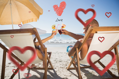Happy couple clinking their glasses while relaxing on their deck chairs against love heart photo