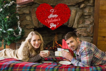 couple lit: Couple with tea cups in front of lit fireplace against cute valentines message Stock Photo