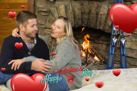 couple lit: Cheerful couple with arms around in front of lit fireplace against happy valentines day Stock Photo