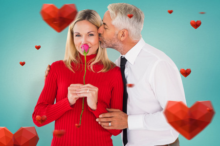 Handsome man giving his wife a kiss on cheek against blue vignette background photo