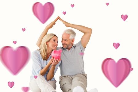 sheltering: Happy couple sitting and sheltering piggy bank against hearts