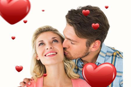 cheek: Handsome man kissing girlfriend on cheek against hearts Stock Photo