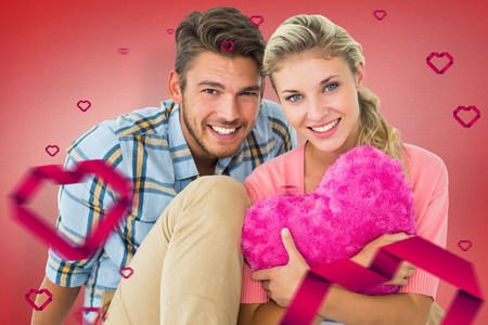 Attractive young couple sitting holding heart cushion against red vignette photo