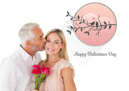 Affectionate man kissing his wife on the cheek with roses against cute valentines message photo