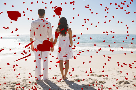 Attractive couple holding hands and watching the waves against love heart pattern photo
