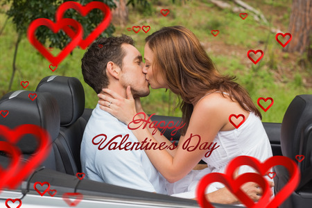 Beautiful couple kissing in back seat against cute valentines message photo