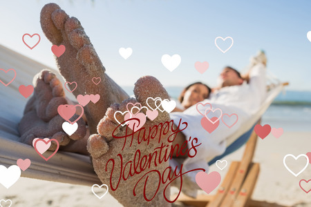 sandy feet: Close up of sandy feet of couple in a hammock against happy valentines day Stock Photo