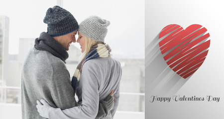 warm clothing: Cute couple in warm clothing hugging against cute valentines message Stock Photo