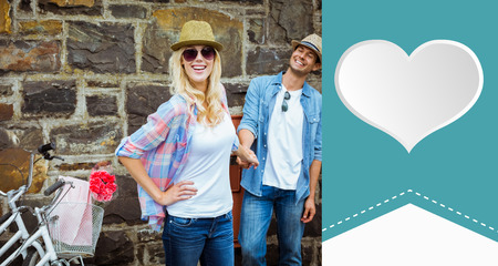 Hip young couple standing by brick wall with their bikes against heart label photo